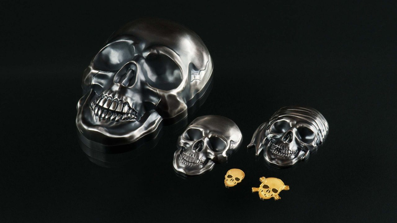 Silver and gold coin shaped like a big skull with smartminting high relief